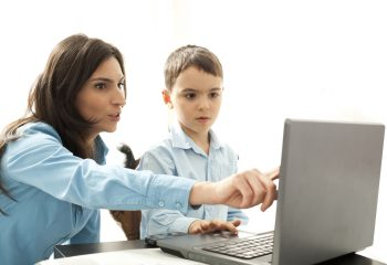 boy leaning to use computer