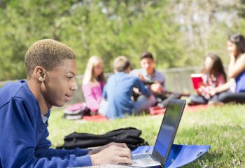 Multi-ethnic group of school friends hang out together on school campus or at local park. They are studying with books and laptops. Mixed-race male student in foreground using laptop computer.